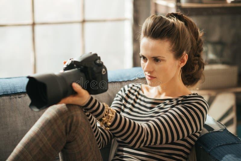 Młoda brunet kobieta jest siedząca dslr kamerę i trzymająca fotografia royalty free