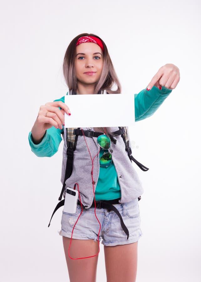 Młoda brunetka żeńskiego ucznia pozycja i słuchanie muzyka od twój przyrządu Piękny młody backpacker zdjęcia stock