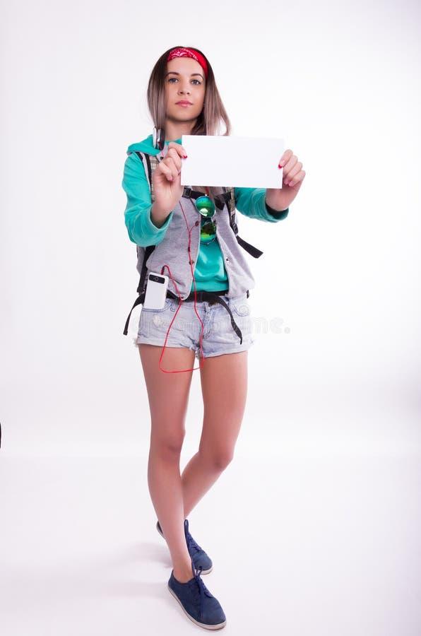 Młoda brunetka żeńskiego ucznia pozycja i słuchanie muzyka od twój przyrządu Piękny młody backpacker zdjęcie royalty free