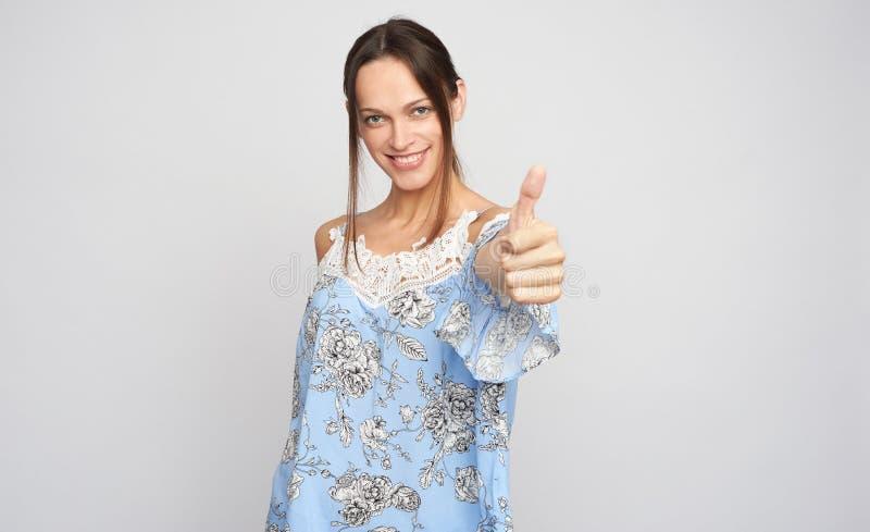 MÅ'oda brunetka pokazuje kciuki w odosobnieniu na szarym fotografia stock