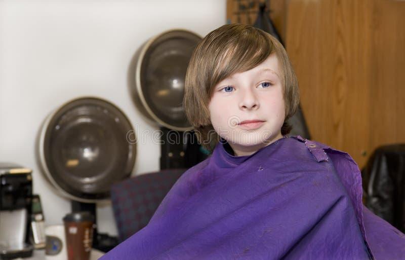 Młoda brunetki chłopiec przy włosianym salonem obraz royalty free