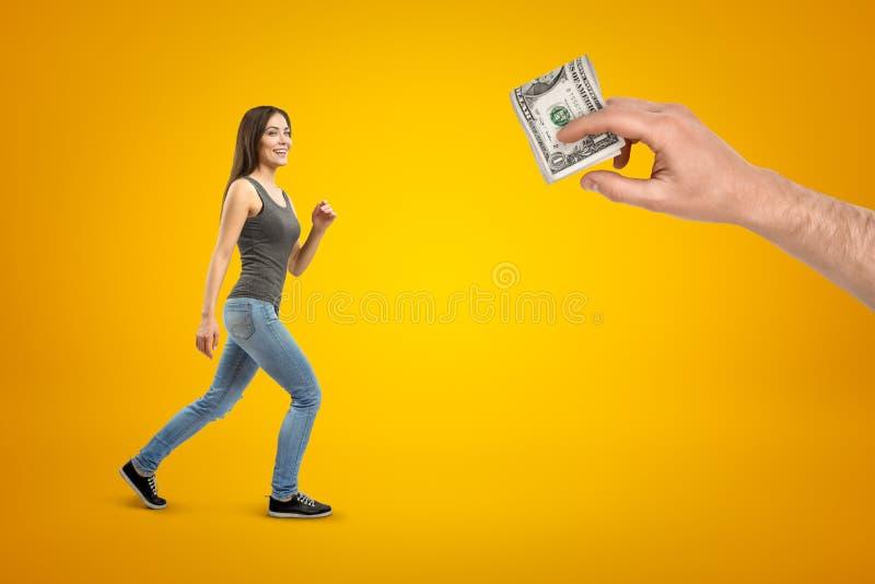 Młoda brunetki dziewczyna jest ubranym przypadkowych cajgi i koszulkę iść męska ręka z pieniędzy dolarami na żółtym tle obrazy stock