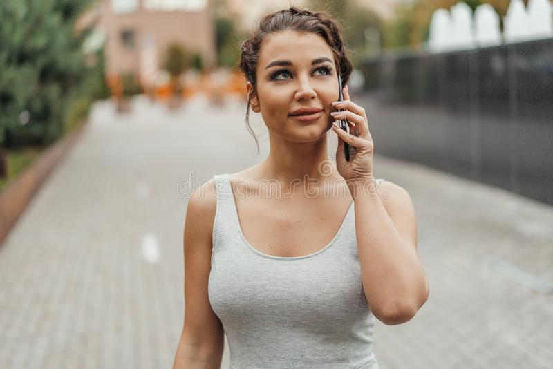 Młoda brunetki dziewczyna opowiada telefonem komórkowym w parku przy lato czasem zdjęcie stock