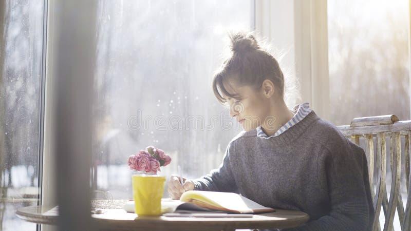 Młoda brunetki dziewczyna pisze puszek notatkach notatnik w kawiarni zdjęcia royalty free