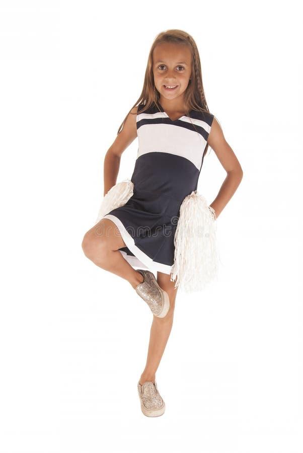 Młoda brunetki dziewczyna w cheerleading stroju z nogą up fotografia royalty free