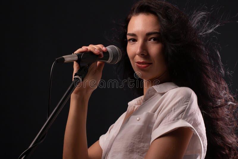Młoda brunetki dziewczyna z długie włosy z mikrofonem zdjęcia stock