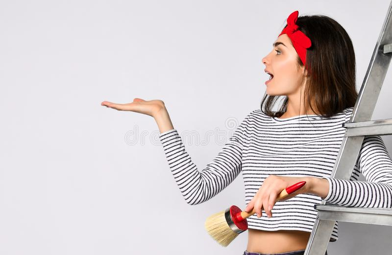 Młoda brunetki dziewczyna z drabiną i muśnięciem - wskazuje przestrzeń dla twój reklamy obrazy royalty free