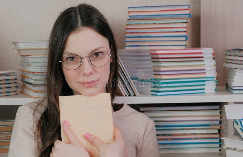 Młoda brunetki kobieta ściska książkę patrzeje kamery obsiadanie wśród książek w szkłach obrazy stock