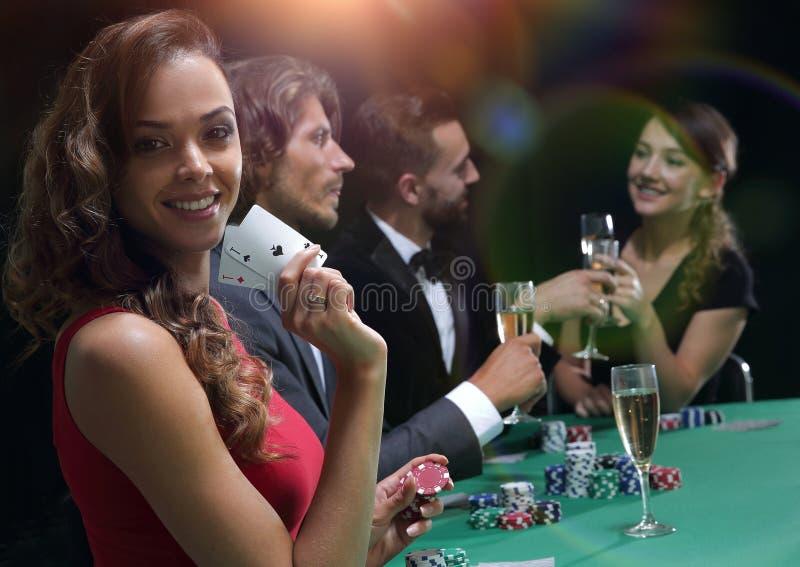 Młoda brunetki kobieta bawić się grzebaka na czarnym tle fotografia stock