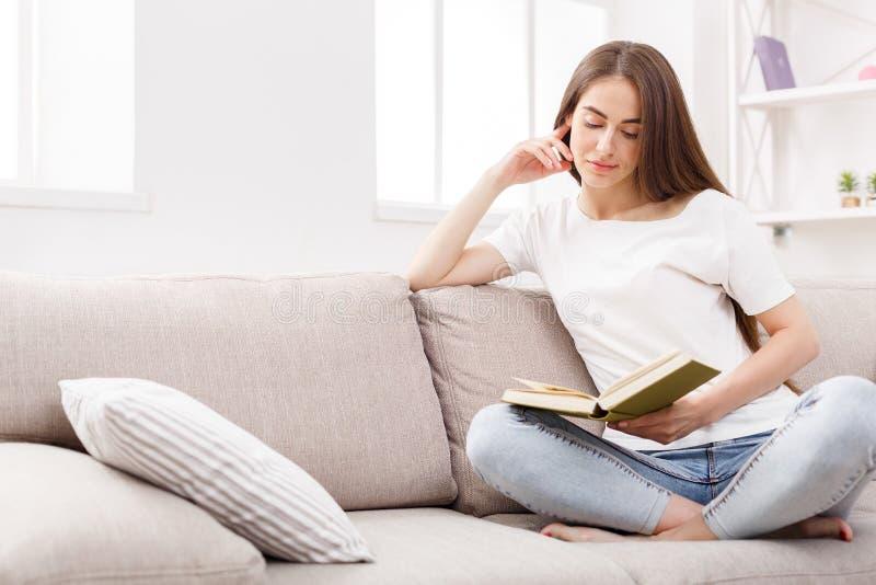 Młoda brunetki kobieta czyta książkę na leżance w domu zdjęcia royalty free
