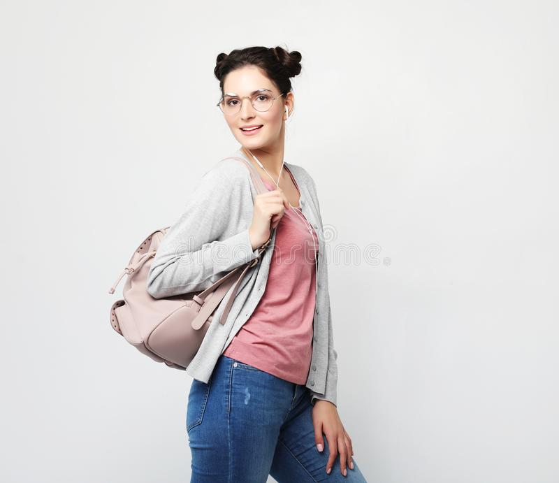 Młoda brunetki kobieta jest ubranym różową koszulkę i cajgi trzyma ono uśmiecha się i plecaka zdjęcie royalty free