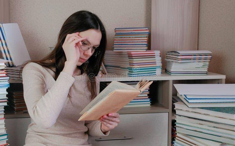 Młoda brunetki kobieta jest ubranym szkła czytających książkowego obsiadanie na podłoga wśród książek zdjęcie stock