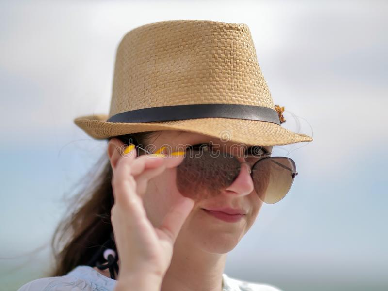 Młoda brunetki kobieta prostuje okulary przeciwsłonecznych na jej twarzy, seksowny spojrzenie, spojrzenia w kamerę zdjęcia royalty free