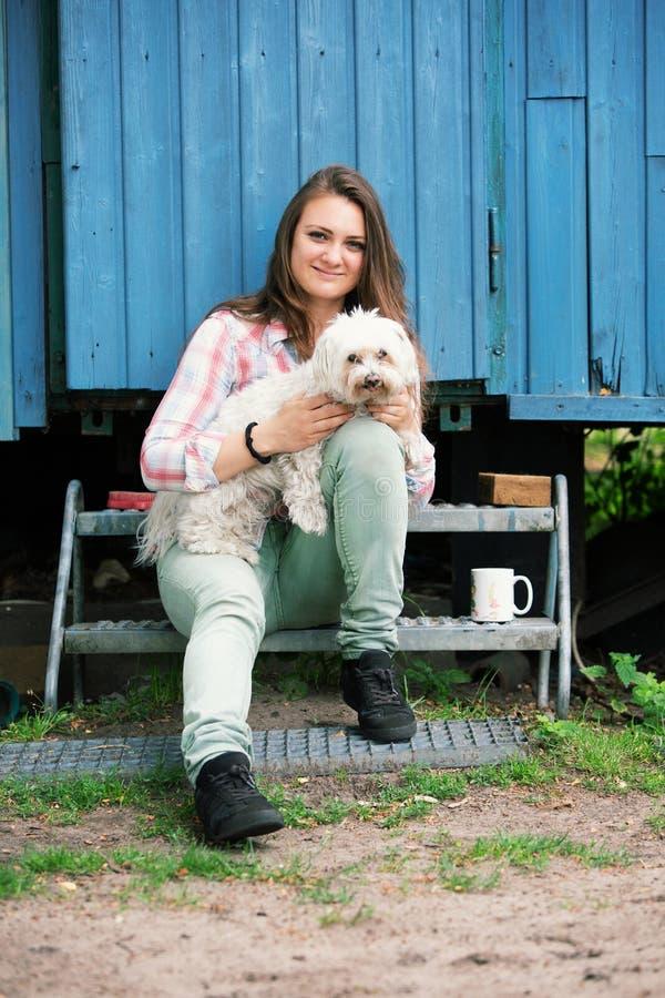 Młoda brunetki kobieta siedzi outdoors z jej małym psem fotografia royalty free