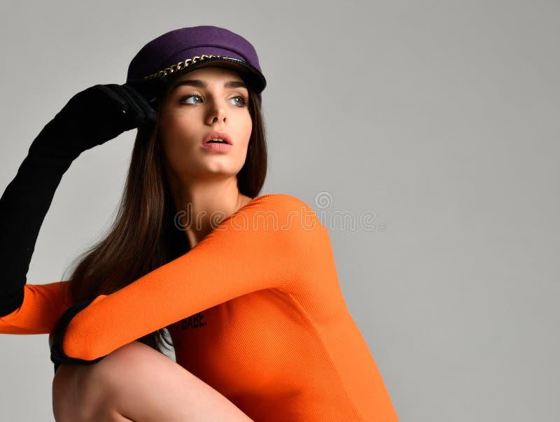 Młoda brunetki kobieta w purpurach osiągać szczyt nakrywa beret w czarnych rękawiczkach, pomarańczowym bluzki obsiadaniu i patrze zdjęcia royalty free