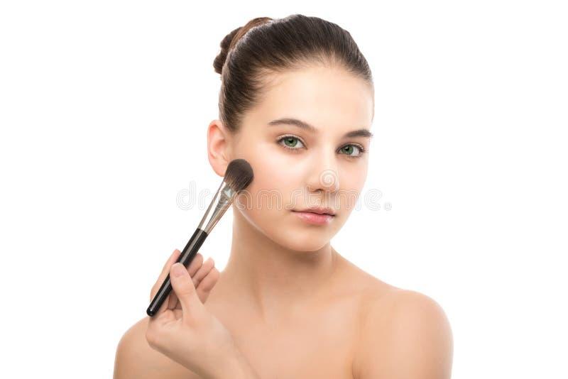 Młoda brunetki kobieta z czystą twarzą Dziewczyny perfect skóra stosuje kosmetyka muśnięcie odosobniony miotła biel zdjęcie stock