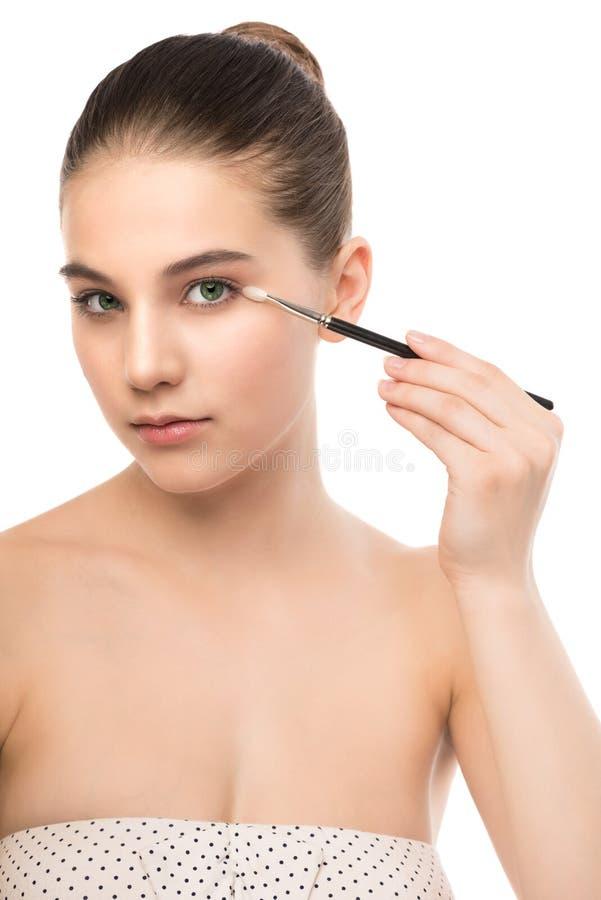 Młoda brunetki kobieta z czystą twarzą Dziewczyny perfect skóra stosuje kosmetyka muśnięcie odosobniony miotła biel obrazy stock