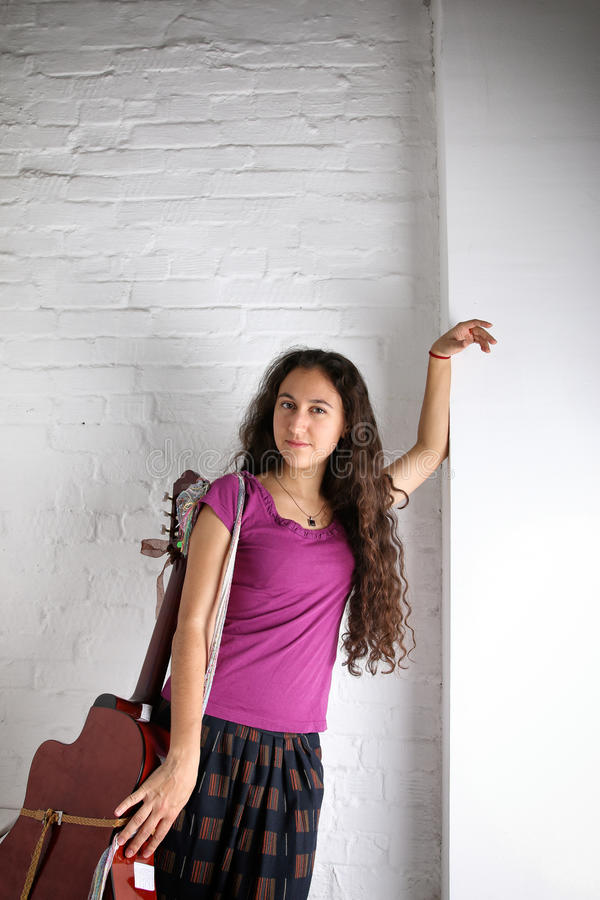 Młoda brunetki kobieta z gitarą akustyczną w długiej spódnicie tło wizerunku rastre ceglana ściana obrazy royalty free