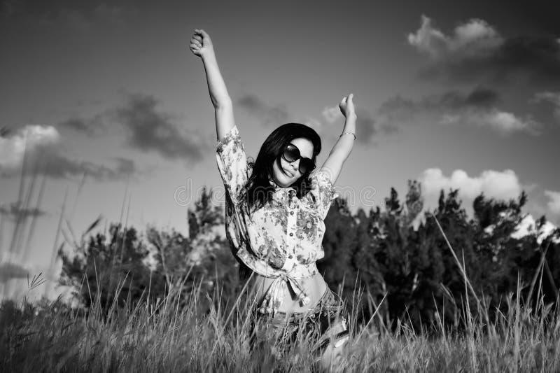 Młoda brunetki kobieta z okularami przeciwsłonecznymi na trawy polu - czerni i fotografia royalty free