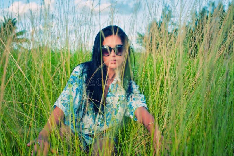 Młoda brunetki kobieta z okularami przeciwsłonecznymi na zielonej trawy polu obrazy royalty free