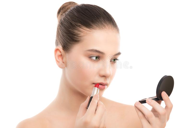 Młoda brunetki kobieta z perfect czystą twarzą stosuje pomadkę używać lustro odosobniony miotła biel zdjęcie stock