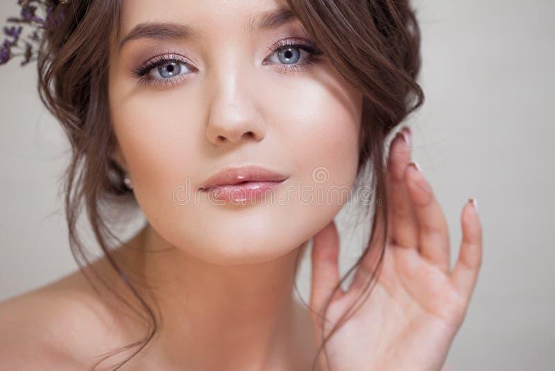 Młoda brunetki kobieta z pięknym wiosny spojrzeniem, fryzura z wyplata i błękit kwitnie zdjęcie royalty free