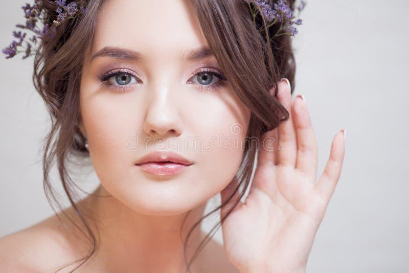 Młoda brunetki kobieta z pięknym wiosny spojrzeniem, fryzura z wyplata i błękit kwitnie zdjęcia stock