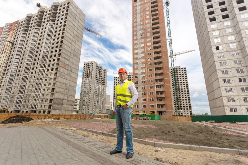 Młoda budowa inżyniera pozycja przed budynkami obrazy royalty free