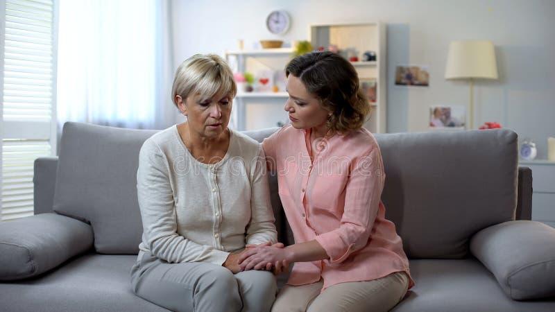 Młoda córka pociesza starej matki, rodzinnych powiązań problemu, poparcia i opieki, zdjęcia stock