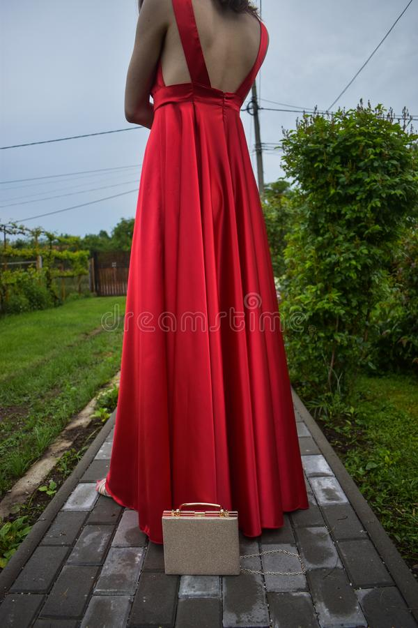 Młoda caucasian dziewczyna jest ubranym elegancką czerwieni suknię z czerwieni różą w jej włosy zdjęcia stock