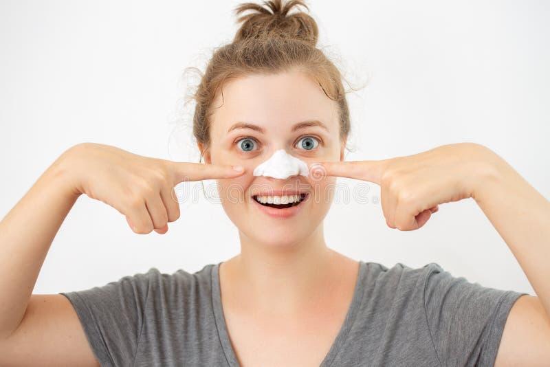 Młoda caucasian kobieta z białą łupy maską na jej nosie, usuwa zaskórniki obraz royalty free