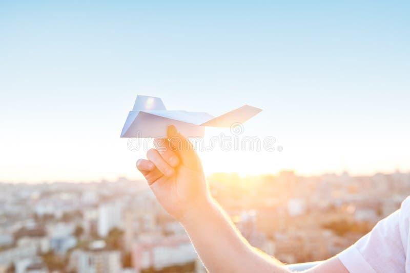 Młoda caucasian mężczyzna ` s ręka trzyma papierowego samolot w niebieskim niebie przy zmierzchu światłem z miasto krajobrazu tłe obrazy stock