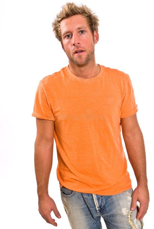 Młoda caucasian samiec w jaskrawej pomarańczowej koszulce i cajgach zdjęcia stock