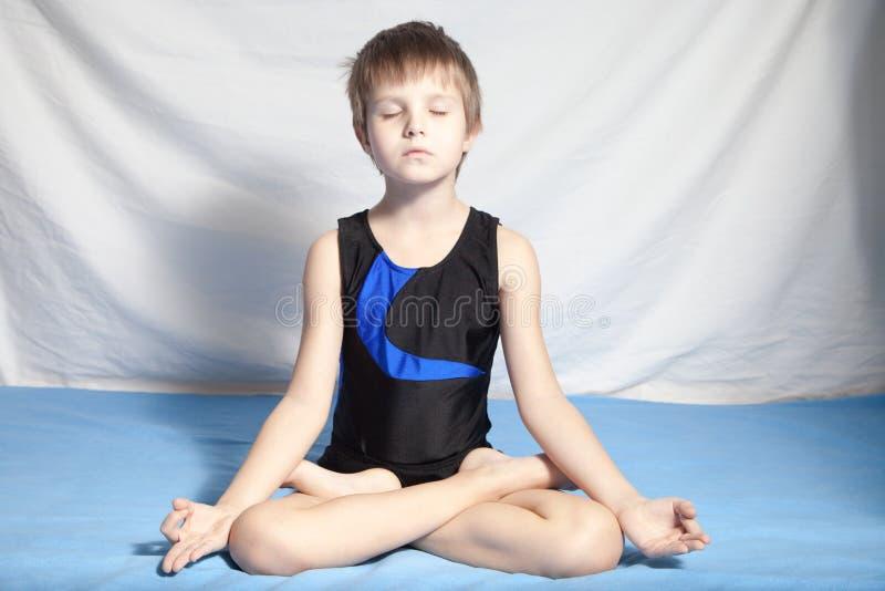 Młoda chłopiec ćwiczy joga zdjęcie stock