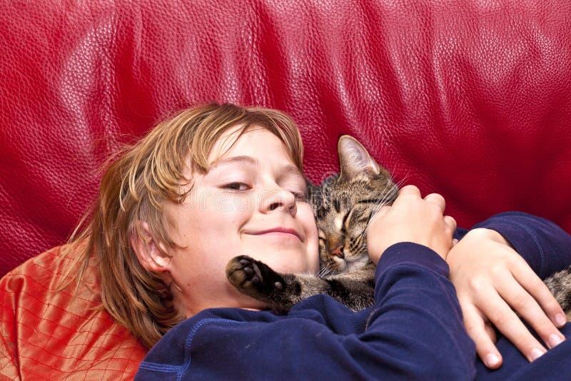 Młoda chłopiec ściska z jego kotem zdjęcie royalty free