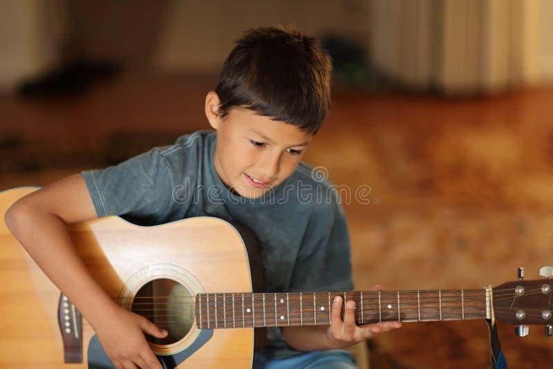 Młoda chłopiec bawić się gitarę fotografia royalty free