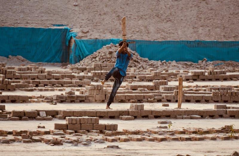 Młoda chłopiec bawić się krykieta wokoło cegły pola w Bangladesz zdjęcie royalty free