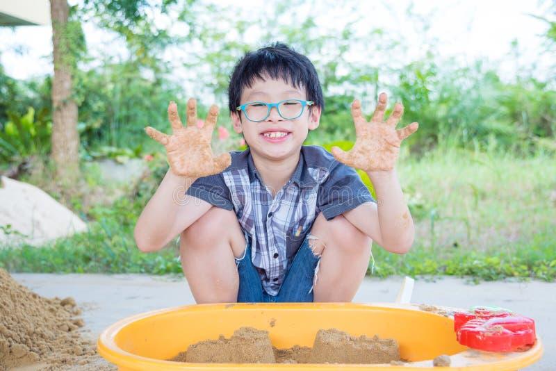 Młoda chłopiec bawić się piasek w piaskownicie obraz stock