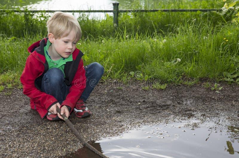 Młoda chłopiec bawić się przy kałużą fotografia stock