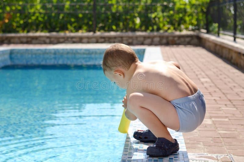 Młoda chłopiec bawić się przy krawędzią pływacki basen fotografia stock