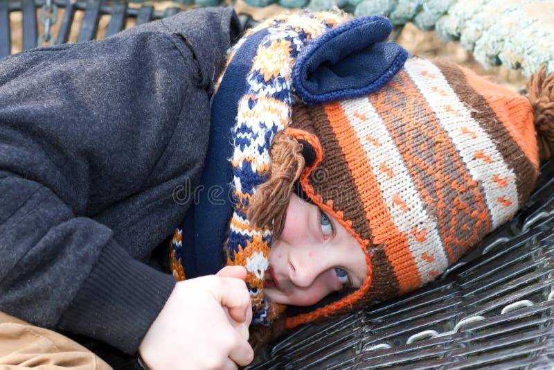 młoda chłopiec bawić się przy parkiem na zimnym dniu obrazy royalty free