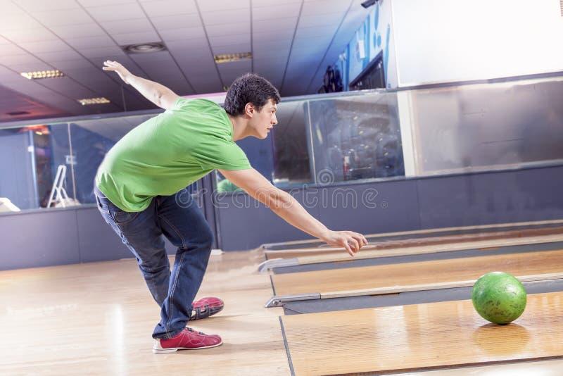 Młoda chłopiec ciągnie piłkę na kręgle alei zdjęcie royalty free