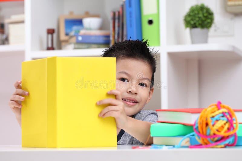 Młoda chłopiec cieszy się jego czytelniczą książkę salowy położenie fotografia stock