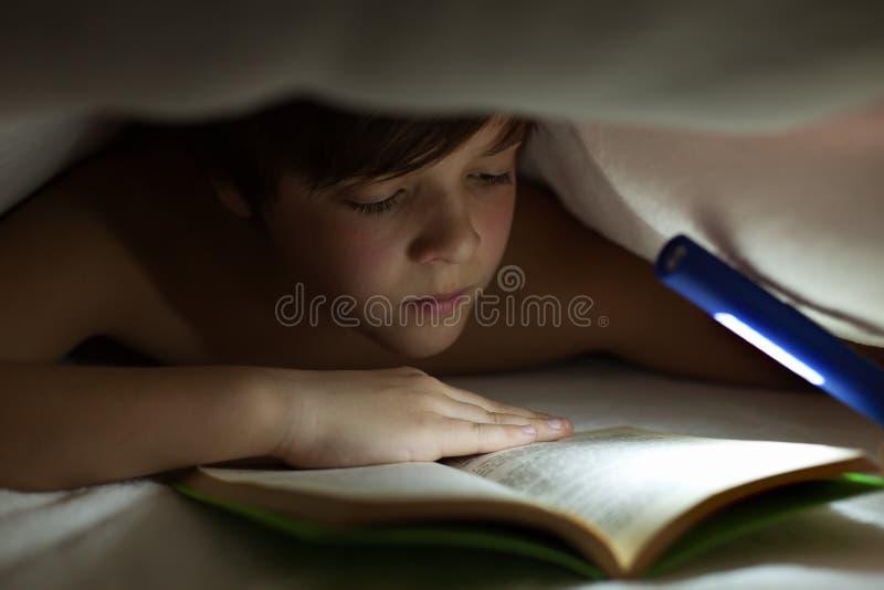Młoda chłopiec czyta książkę pod kołderką lub koc obraz stock