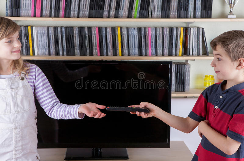 Młoda chłopiec daje pilot do tv jego siostra przed th zdjęcie stock