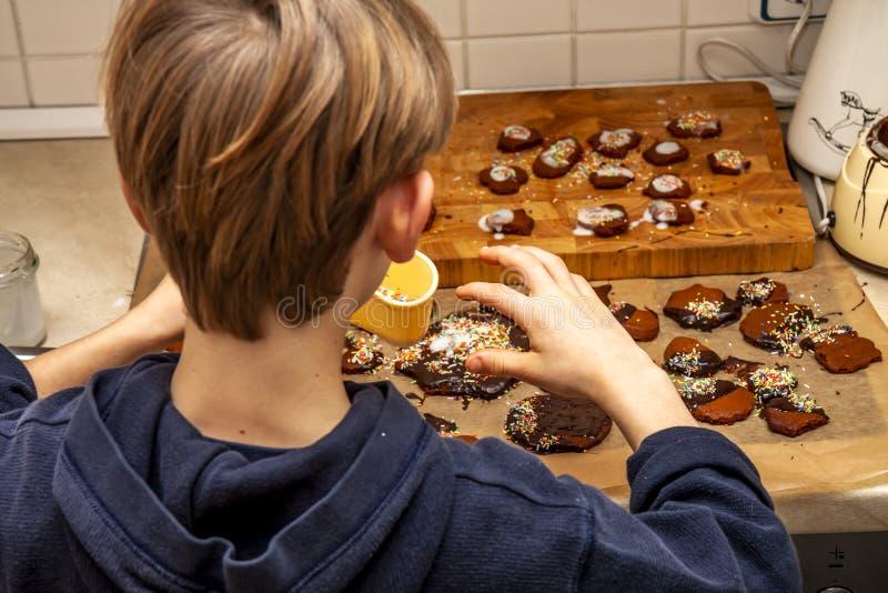 Młoda chłopiec dekoruje ciastka w kuchni zdjęcie royalty free
