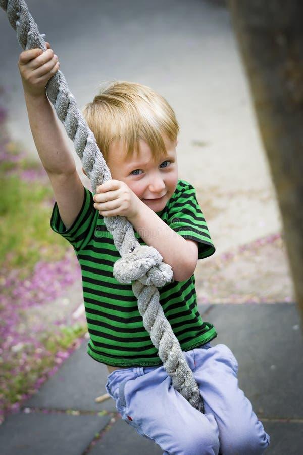 Młoda chłopiec huśta się na arkanie przy parkiem fotografia royalty free