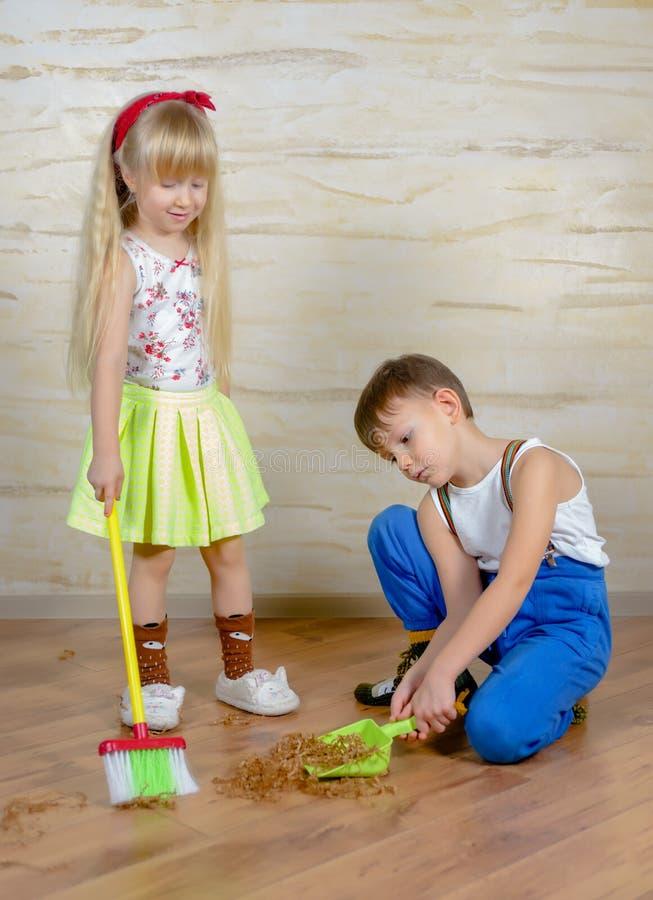 Młoda chłopiec i dziewczyna pomaga czyścić dom zdjęcie royalty free