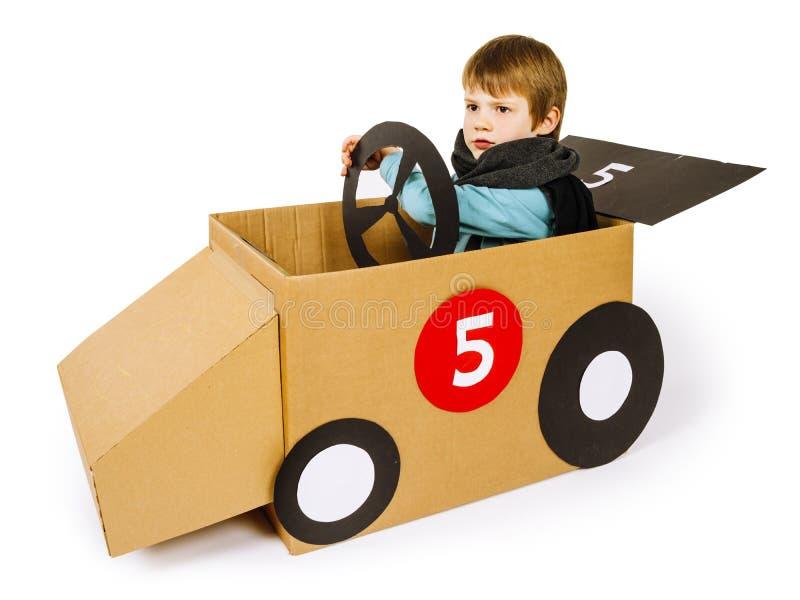 Młoda chłopiec jedzie jego kartonowego samochód zdjęcia stock