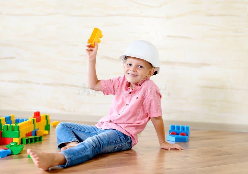 Młoda chłopiec jest ubranym hardhat bawić się indoors zdjęcie royalty free
